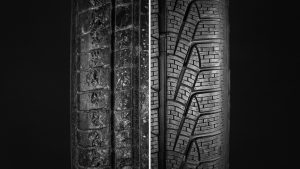 Comparing a new tire with an old, worn out tire.