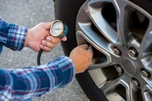 Checking tire pressure with pressure gauge.