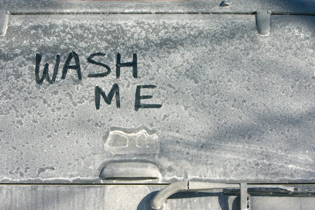 "The words ""Wash me"" written on a car covered in salt that needs a clean"