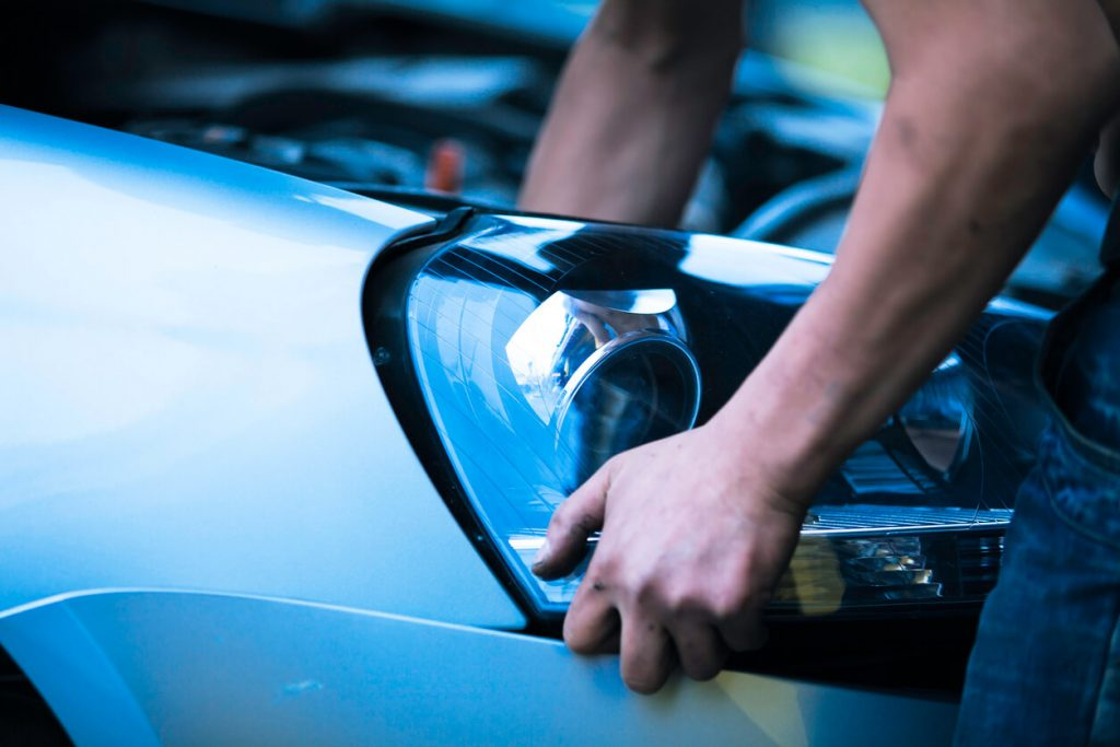 Used headlight is being installed by auto mechanic in Ontario