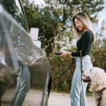 Woman with her dog charging her electric vehicles.